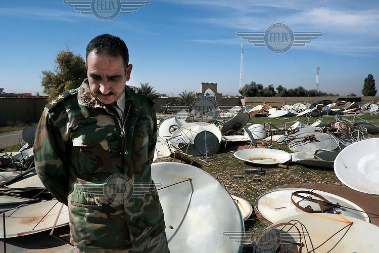First lieutenant Naser, from the Kakai religious minority, stands among dozens of satellite dishes that had been confiscated by ISIS millitants from residents in the village of Khidr Ilyas. Behind him is the Mar Behnam Monastery that ISIS millitants converted into a headquarters.