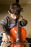 Elementary School New York male kindergarten student arts enrichment music boy playing cello during lesson vertical