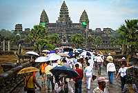 Tourists' umbrellas in a  late afternoon rainstorm provide a colorful foreground to an iconic temple.