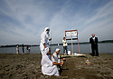 The priest, the groom, and a religious witness say some prayers while family members hang around the beach at Kensington Metro Park during different phases of A Mandean ritual baptism.