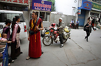 CHINA. Han police officers (rear, in blue) are everpresent in a market frequented by Tibetans and Muslims. Increased surveilance has appearaed in the wake of unrest in the west of the country in recent years. 2010