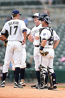 NW Arkansas Naturals pitching coach Jim Brower (38) talks with pitcher Sam Selman (17) and catcher Micah Gibbs (27) during a game against the Corpus Christi Hooks on May 26, 2014 at Arvest Ballpark in Springdale, Arkansas.  NW Arkansas defeated Corpus Christi 5-3.  (Mike Janes/Four Seam Images)