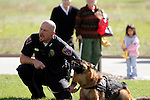 Police Officer with his K-9 partner yelling at a suspect while the dog continues to bark at a demonstration at a safety fair