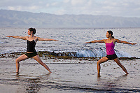 Young women practicing yoga poses at Shark's Cove on the North Shore of Oahu