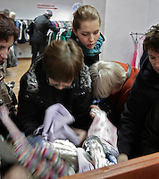 "Customers, (Melanie Kucharska, 21, top),  search for used clothes at the ""Kiermasz Odziezy"" second hand clothes shop December 1, 2008 in Warsaw, Poland..Second hand clothes become fashionable among younger generation of Poles who, even if they can afford new clothes, like to search for something less usual. Older people rather come to such shops because of low pension. ..Every two weeks there is a full change of stock and a crowd storms the shop in the first morning...(Photo by Piotr Malecki)"