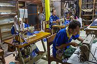 Yogyakarta, Java, Indonesia.  Batik Workshop.  Men and Women Sewing Fabric.