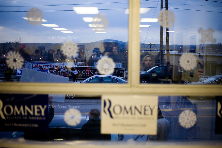 Romney supporters wave signs to traffic outside the Mitt  Romney New Hampshire campaign headquarters in Manchester, New Hampshire, on Jan. 7, 2012. Romney is seeking the 2012 Republican presidential nomination.