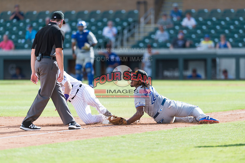 Surprise Saguaros third baseman Vladimir Guerrero Jr. (27), of the Toronto Blue Jays organization, looks to third base umpire Bryan Fields after applying a tag to Tyler Nevin (2) during an Arizona Fall League game against the Salt River Rafters at Salt River Fields at Talking Stick on October 23, 2018 in Scottsdale, Arizona. Salt River defeated Surprise 7-5 . (Zachary Lucy/Four Seam Images)