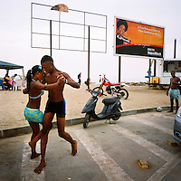 A young couple dance on a street by the beach on the Ilha de Luanda on a Sunday afternoon. In the background is a billboard advertisement for Inecto Super Black hair colourant..