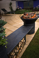 Lighted Firepit with flames on patio in outdoor lifestyle garde,n modern, firewood, garden wall, flowers, grass lawn, furniture, night garden illumination, heat and cooking, with bench