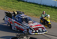 Aug 15, 2014; Brainerd, MN, USA; NHRA funny car driver John Force rides a scooter alongside the car of daughter Courtney Force during qualifying for the Lucas Oil Nationals at Brainerd International Raceway. Mandatory Credit: Mark J. Rebilas-