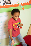 Education preschool 4-5 year olds boy with special needs throwing up toy hypodermic, playing by himself