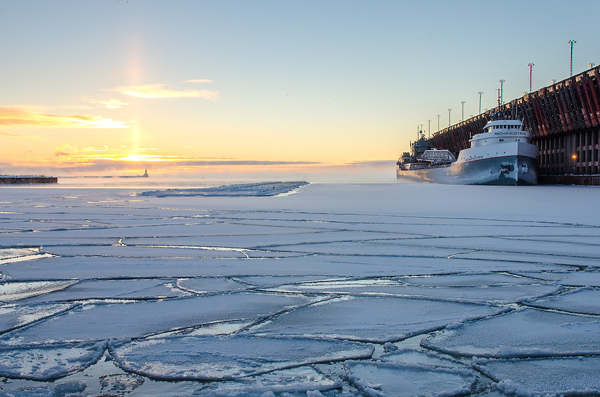 A sub-zero Lake Superior sunrise at the Upper Harbor Iron Ore Dock in Marquette, MI. The Great Lakes freighter the Michipicoten is docked in the icy water.
