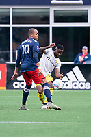 FOXBOROUGH, MA - MAY 16: Waylon Francis #14 Columbus SC passes the ball under pressure from Teal Bunbury #10 of New England Revolution during a game between Columbus SC and New England Revolution at Gillette Stadium on May 16, 2021 in Foxborough, Massachusetts.