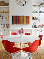 A more family friendly dining area with an Eero Saarinen table and red Eames chairs