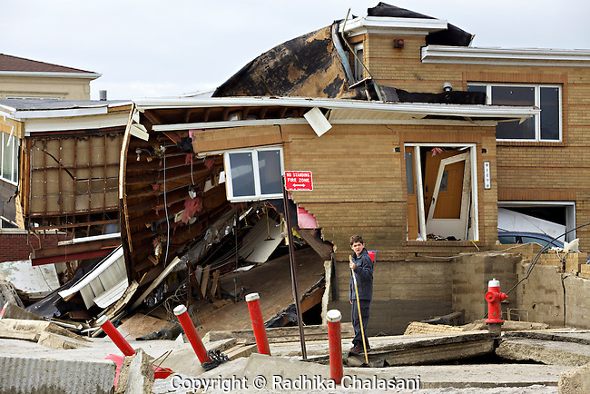 BELLE HARBOR, NEW YORK-NOVEMBER 1: A young boy stands in front of a destroyed home on the beach in this Rockaway, Queens neighborhood after Hurricane Sandy November 1, 2012. A large number of homes and businesses were destroyed by the storm and much of the area is without power.