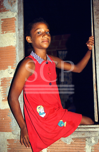 Bahia, Brazil. Young girl wearing a red dress sitting on the sill of a window in a rough brick house.