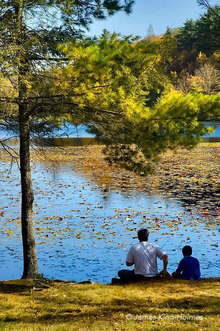 Man and boy sitting by lake-side