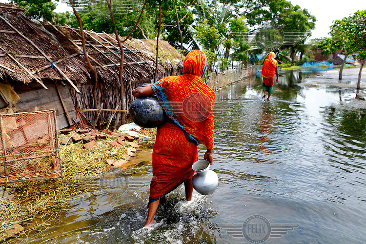 A woman carries pots of water through flood waters that have innundated the Satkhira district. Each year limited flooding helps to enrich the soil and create very fertile farm land. In turn, this results in a high population density on the flood plain. However, the low lying land is also prone to extreme flooding events that are very destructive to both the economy and human life.