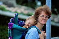 Grandmother carrying her sleeping grandson in a backpack.