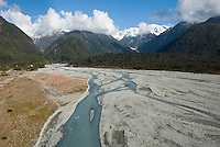 Looking into a valley across braided Waiho River with Franz Josef Glacier lurking right of centre. A township on a left  - Westland National Park, West Coast