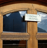 """A sign reading """"gone skiing' hangs on the front door of a chalet"""