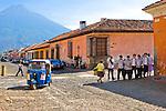 A group of Guatemalan students walk down a cobblestoned street in Antigua, Guatemala