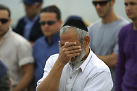 """An unidentified man mourns at the funeral of Danit Dagan, 24, and Uri Felix, 28. in Jerusalem's Givat Shaul cemetery March 10, 2002, the morning after they were killed in a Palestinian suicide bombing in Jerusalem's """"Moment"""" coffe shop. Eleven Israelis were killed in the bombing."""