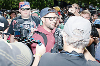 A counter-protester (in hat) snuck into barricades keeping marchers and protesters apart before the Straight Pride Parade in Boston, Massachusetts, on Sat., August 31, 2019. The parade was organized in reaction to LGBTQ Pride month activities by an organization called Super Happy Fun America.