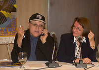 Daniele Cauchard, V-P World Film Festival (R) look at Serge Losique, President World Film Festival<br /> answering  his cell phone during a  press conference, <br /> July 31 2003  in Montreal, CANADA.<br /> <br />  File Photo Agence Quebec Presse - Pierre Roussel
