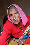 An elderly woman pauses while rolling out pappadums in her kitchen.