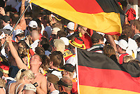 Before the semi-final match between Germany and Italy, a German national soccer team supporters waves a large German Flags at the Fan Festival next to the Brandenburg Gate in Berlin Germany, on July 4th, 2006. The FIFA World Cup Semi-Final match was won on two late goals in extra-time by Italy, which defeated Germany to advance to the final.