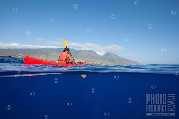A young man paddling a kayak off the coast of Maui.
