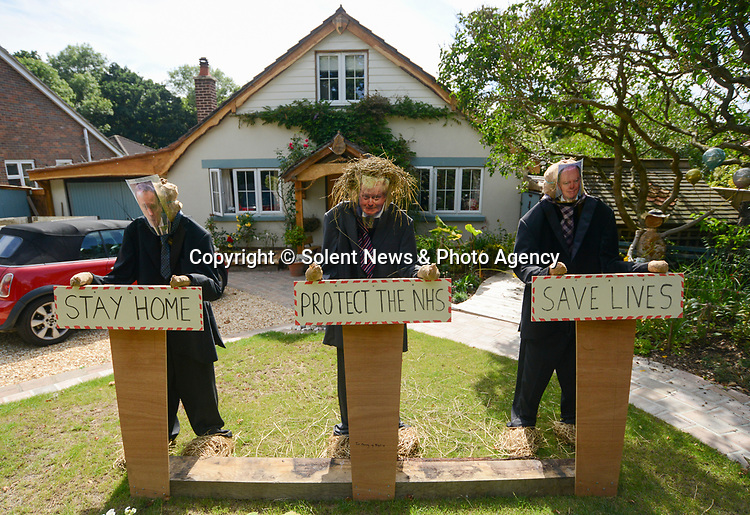 SCARECROW VILLAGE FESTIVAL IN HORDLE, HAMPSHIRE.<br /> <br /> Pictured: Daily Briefing - Entry No.4 for the Hordle Scarecrow compeition.<br /> <br /> Entries this year to a village scarecrow competition seem to have taken a Covid-19 theme, with entries showing Dominic Cummings holding a steering wheel next to an eye chart, key workers stood 2 metres apart and politicians stood at lecterns.<br /> <br /> The pandemic appears to have also played a part in the number of entries this year which is down from twenty last year to eight, but families and businesses have still produced a range of scarecrows for the competition.<br /> <br /> The competition this year is raising money for PATCH - Parents and Teachers in the Community of Hordle, and is organised by the Hordle and District Twinning Association.<br /> <br /> © Ewan Galvin/Solent News & Photo Agency<br /> UK +44 (0) 2380 458800