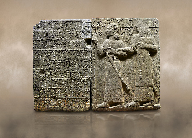 """Photo of Hittite monumental relief sculpted orthostat stone panel of Royal Buttress. Basalt, Karkamıs, (Kargamıs), Carchemish (Karkemish), 900-700 B.C. Anatolian Civilisations Museum, Ankara, Turkey.<br /> <br /> Hieroglyph panel (left) - Discourse of Yariris. Yariris presents his predecessor, the eldest son Kamanis, to his people. <br /> Right Panel - King Araras holds his son Kamanis from the wrist. King carries a sceptre in his hand and a sword at his waist while the prince leans on a stick and carries a sword on his shoulder. <br /> <br /> Hieroglyphs reads; """"This is Kamanis and his siblings.) held his hand and despite the fact that he is a child, I located him on the temple. This is Yariris' image"""".  <br /> <br /> Against a brown art background."""