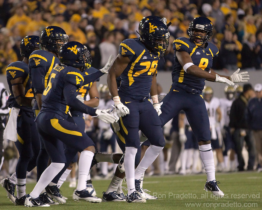 WVU defensive back Terence Garvin (28) gets congratulations from Keith Tandy (8) following a tackle.  The WVU Mountaineers beat the Pitt Panthers 21-20 at Mountaineer Field in Morgantown, West Virginia on November 25, 2011.