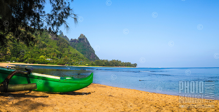 Tunnels Beach, with a green outrigger canoe in the foreground and beachgoers and Mt. Makana (or Bali Hai) in the distance, Kaua'i.