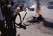Port-au-Prince, Haiti.November 25, 1987..The street burning of a suspected ton-ton-macoute prior to elections being held on November 29th, the first attempt at a democratic election in Haiti. It was unsuccessful as 34 people were killed at a polling station and elections were moved up to February 1988...Leslie François Manigat won the election with many political parties boycotting. He had military backing but once in office he sought greater control over the military in an effort, to fight corruption. Manigat's government was overthrown by General Henri Namphy within months.