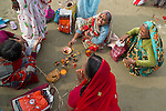 Indian women in traditional dress preparing an offering in Allahabad for Kumbh Mela Festival.