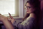 Portrait of a young smiling woman in reading glasses sitting with an iPhone in her hands in a chair by the window, texting, messaging concept