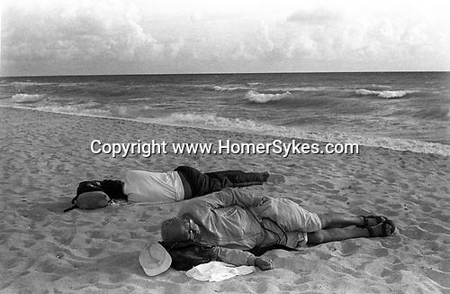 Two men asleep on the beach. Miami, South Beach, Florida. USA. 1999