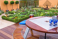 Edible landscaping: Vegetable Garden with deck, garden furniture, table, bench, peppers, wall, backyard, growing food at home, privacy wall, standard laurels in container pots, rustic iron tree ornament on wall, wood decking, patio