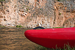The bow of a red kayak on shore of the Smith River in Montana with a rock wall across the river