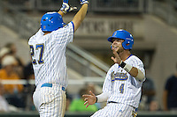 UCLA outfielder Eric Filia (4) is greeted by first baseman Pat Gallagher (27) as he scores a run during Game 12 of the 2013 Men's College World Series against the North Carolina Tar Heels on June 21, 2013 at TD Ameritrade Park in Omaha, Nebraska. The Bruins defeated the Tar Heels 4-1, to reach the CWS Final and eliminate North Carolina from the tournament. (Andrew Woolley/Four Seam Images)