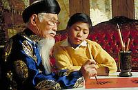 VIETNAMESE-AMERICAN ELDER TEACHING CALLIGRAPHY TO A TEEN STUDENT. VIETNAMESE-AMERICAN TEACHER AND PUPIL. SAN JOSE CALIFORNIA USA.