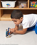 Education preschool 4 year olds boy playing by himself with human figures talking and having adult kiss baby