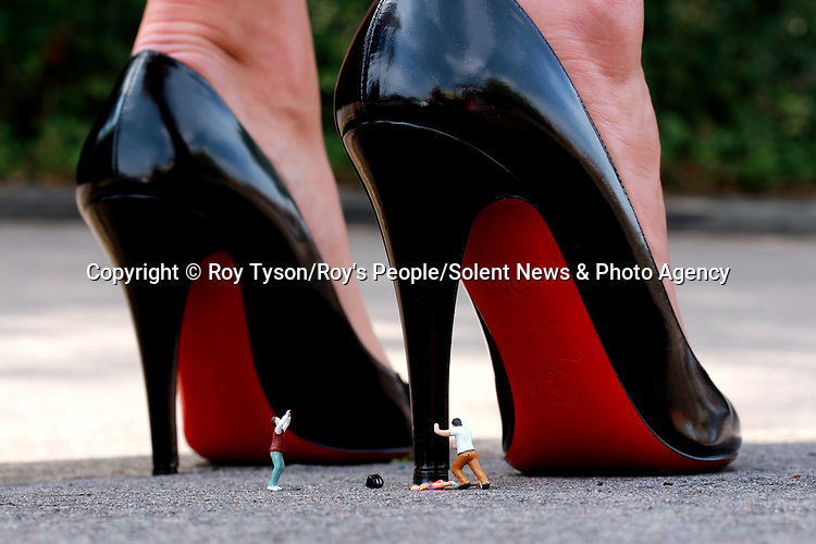 Pictured:  Killer Heels<br /> <br /> Tiny figurines give a new perspective on everyday objects as they are posed interacting with them in their miniature world.  Artist Roy Tyson creates witty and intriguing imagery with customised miniature figures, under the name Roy's People.<br /> <br /> Since 2012, he has been photographing his miniature world on the streets of London and beyond.  SEE OUR COPY FOR DETAILS.<br /> <br /> Please byline: Roy Tyson/Roy's People/Solent News<br /> <br /> © Roy Tyson/Roy's People/Solent News & Photo Agency<br /> UK +44 (0) 2380 458800