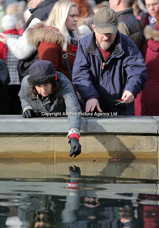 Pictured: A man and a woman deposit poppies in the fountain Friday 11 November 2016<br /> Re: Remembrance Day service at Castle Square Gardens in Swansea, south Wales, UK.