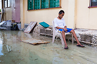 A young boy sits forlornly outside his home which is being flooded during the king tides in Funafuti, Tuvalu. The king tides are seasonal and are characterised by very high water levels in the surrounding ocean. At this time of year the waves inundate the coastline but also water seeps up through the ground which is made of porous coral. This natural phenomenon is particularly serious for Tuvalu, a low-lying atoll island nation, whose highest point is only a few metres above sea level. As sea levels rise, the king tides regularly flood parts of the island and will likely increase in severity in the future, potentially making large parts of the nation uninhabitable. March, 2019.