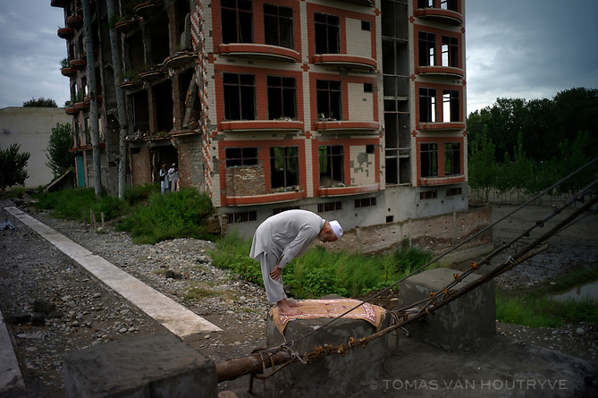 Man muslim man prays in front of a building that was destroyed by a Taliban suicide bomb attack in 2008 in Mingora, Swat valley, Pakistan, on Aug. 26, 2010. At the man's left side was the building destroyed by Islamic militants, and on his right side was a bridge destroyed by heavy flooding.
